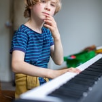 boy in blue and white stripe crew neck t-shirt playing piano