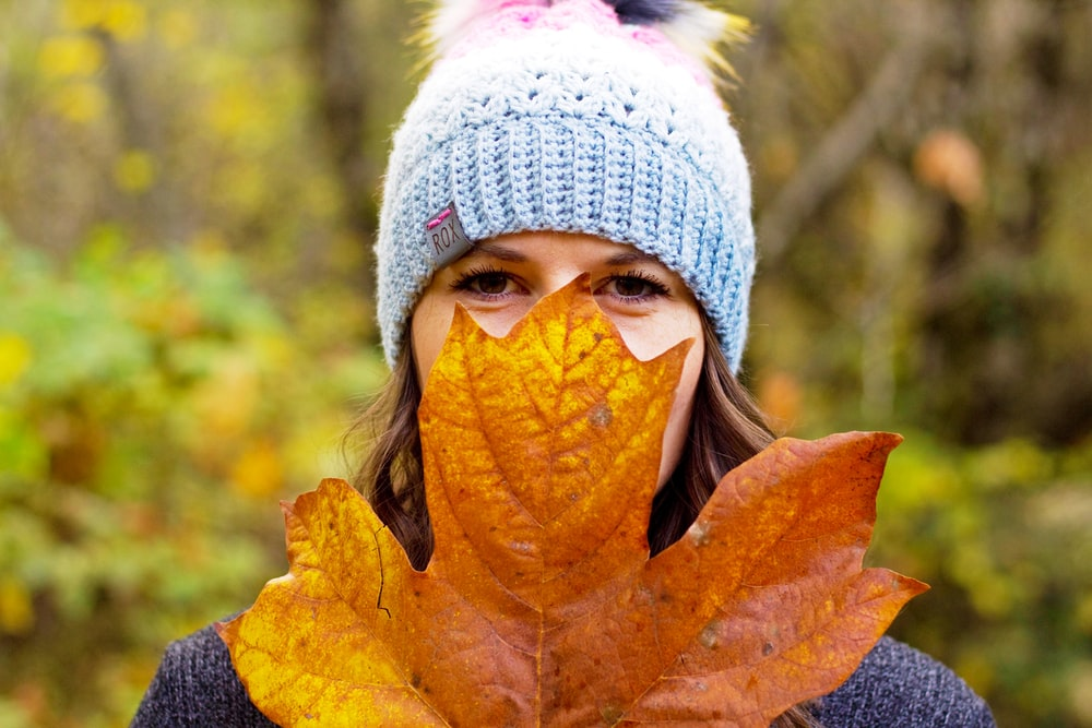 woman in white knit cap covering her face with brown leaf