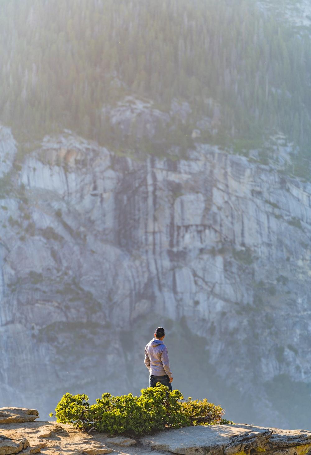 man in white shirt standing on gray rock mountain during daytime