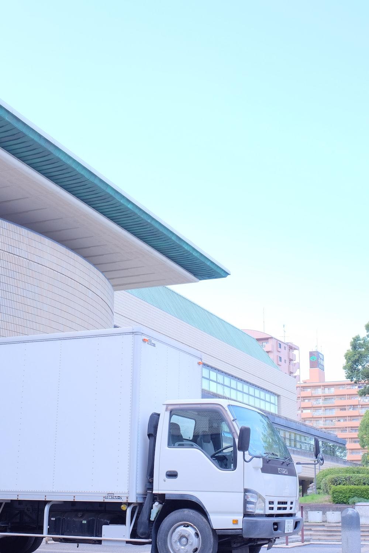 white van parked near white building during daytime