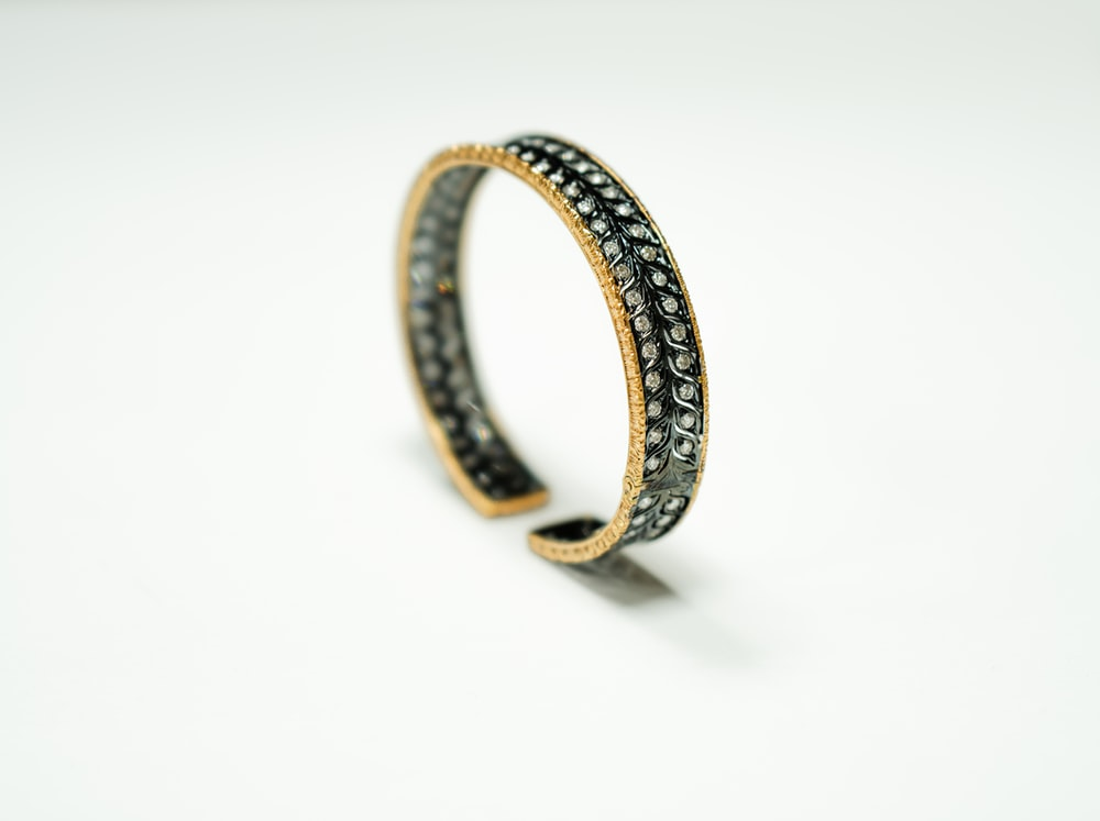 gold and silver ring on white surface