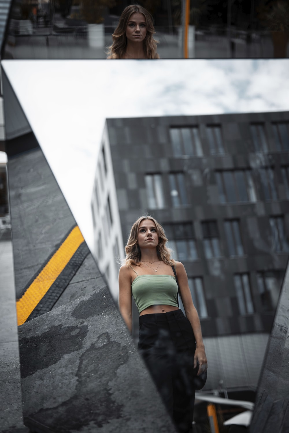 woman in green tube dress standing on gray concrete floor during daytime