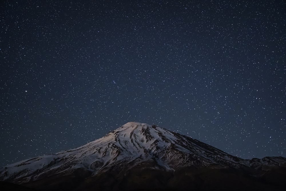 black and white mountain under starry night