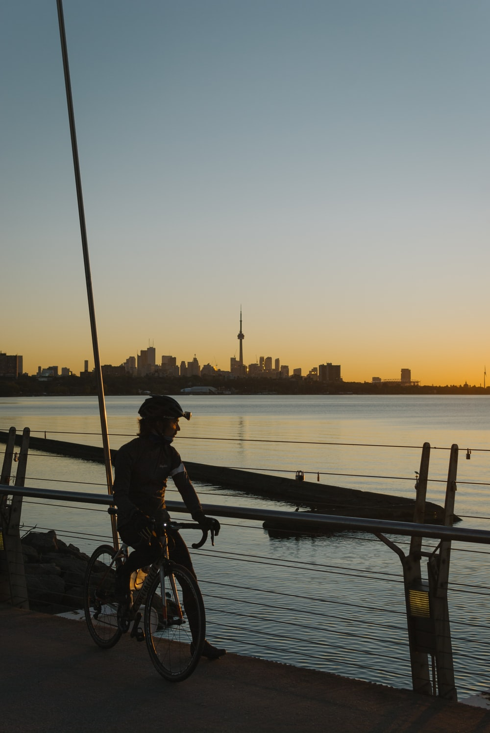 man in black jacket riding bicycle near body of water during sunset