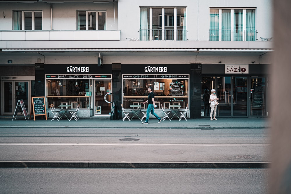 people walking on sidewalk near store during daytime