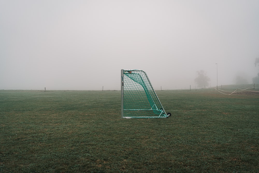 green and white soccer goal net on green grass field