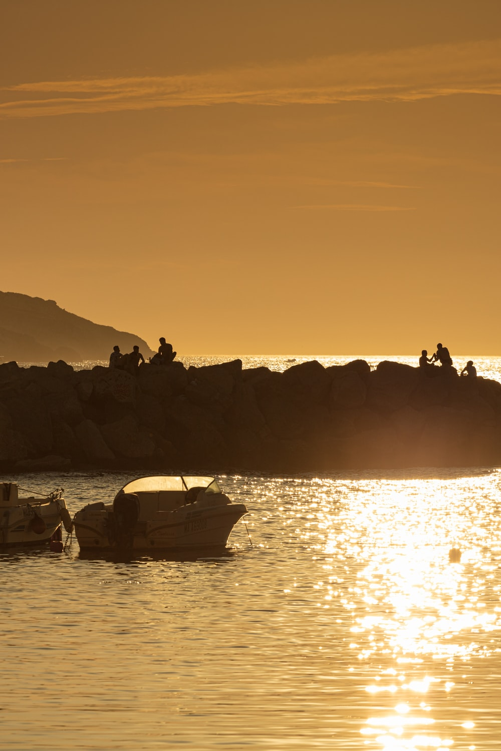silhouette of people on boat on water during sunset