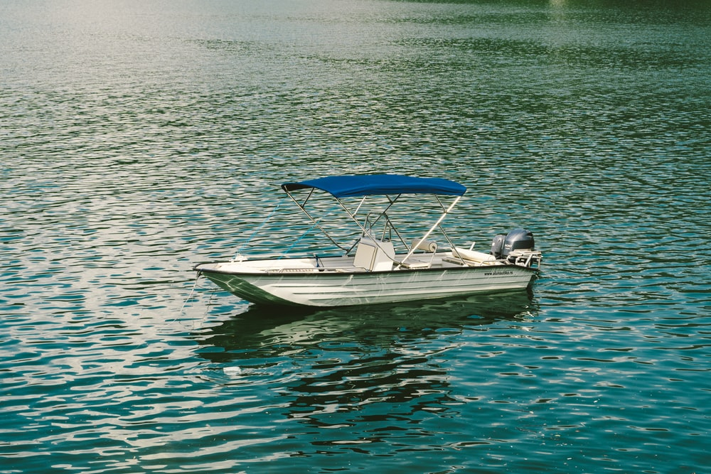 white and blue boat on body of water during daytime