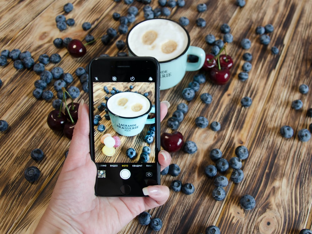 person holding black iphone 4 taking photo of coffee beans on brown wooden table