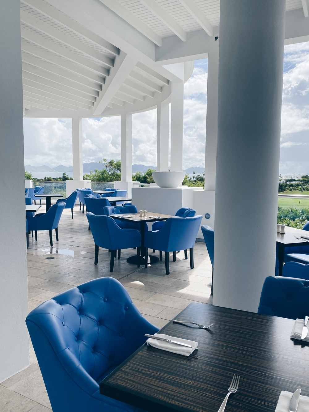 blue chairs and table near glass window