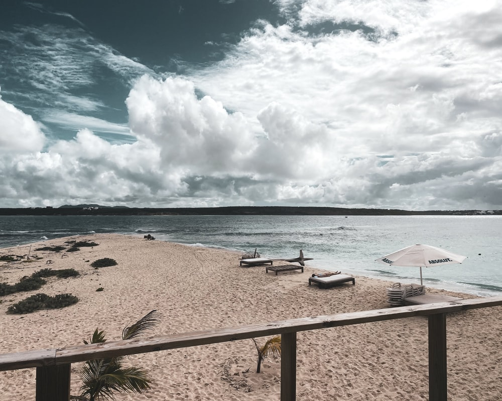 white and black beach lounge chairs on beach shore under blue and white sunny cloudy sky