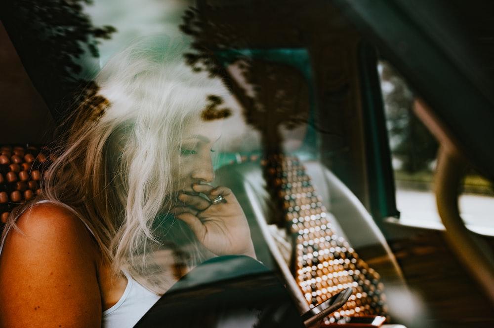 woman in white tank top sitting on car seat