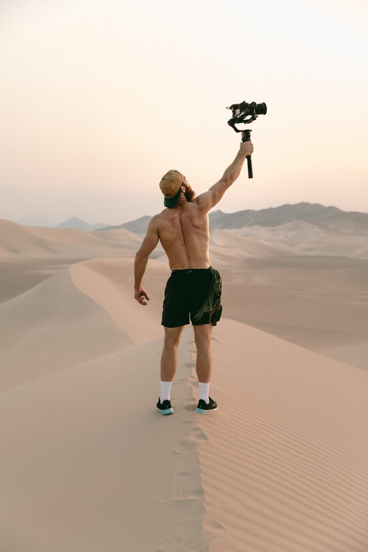 man in black shorts holding black dslr camera