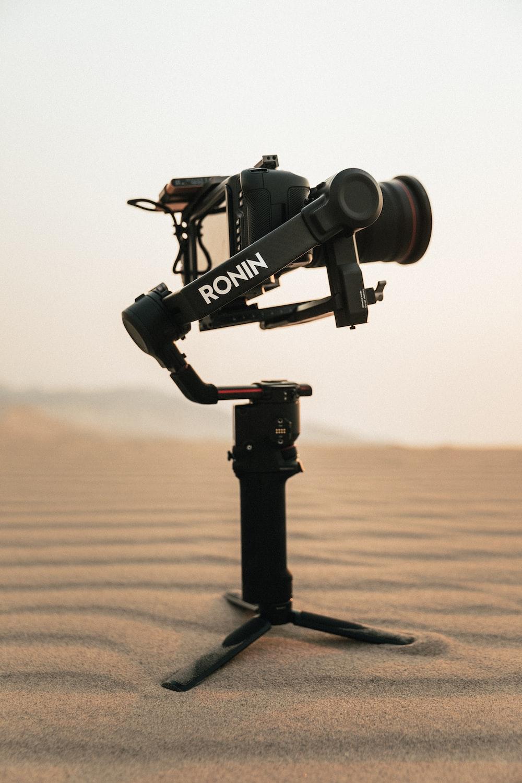 black camera on tripod on brown sand during daytime