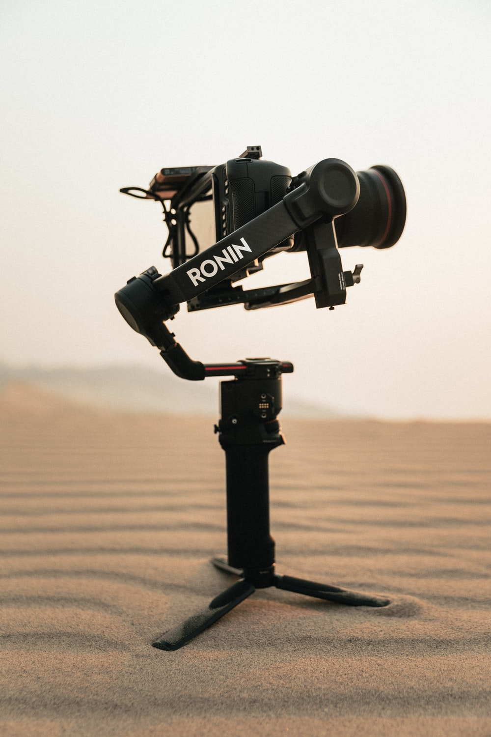 black camera on tripod on brown sand during daytime