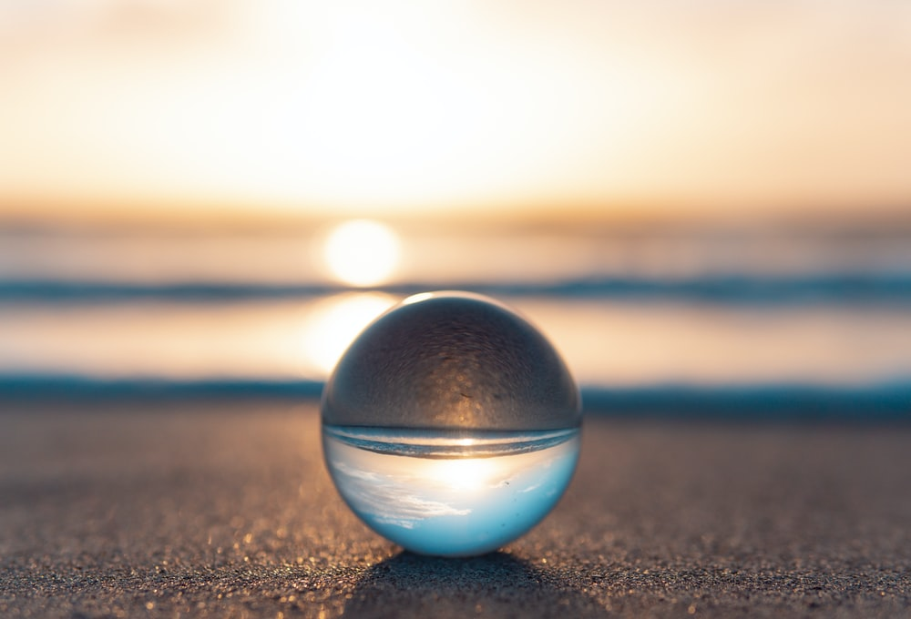 blue and silver ball on black sand