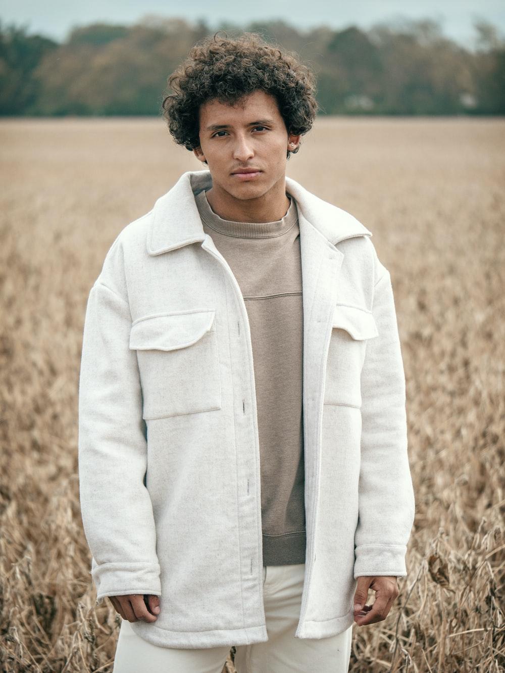 man in white coat standing on brown grass field during daytime