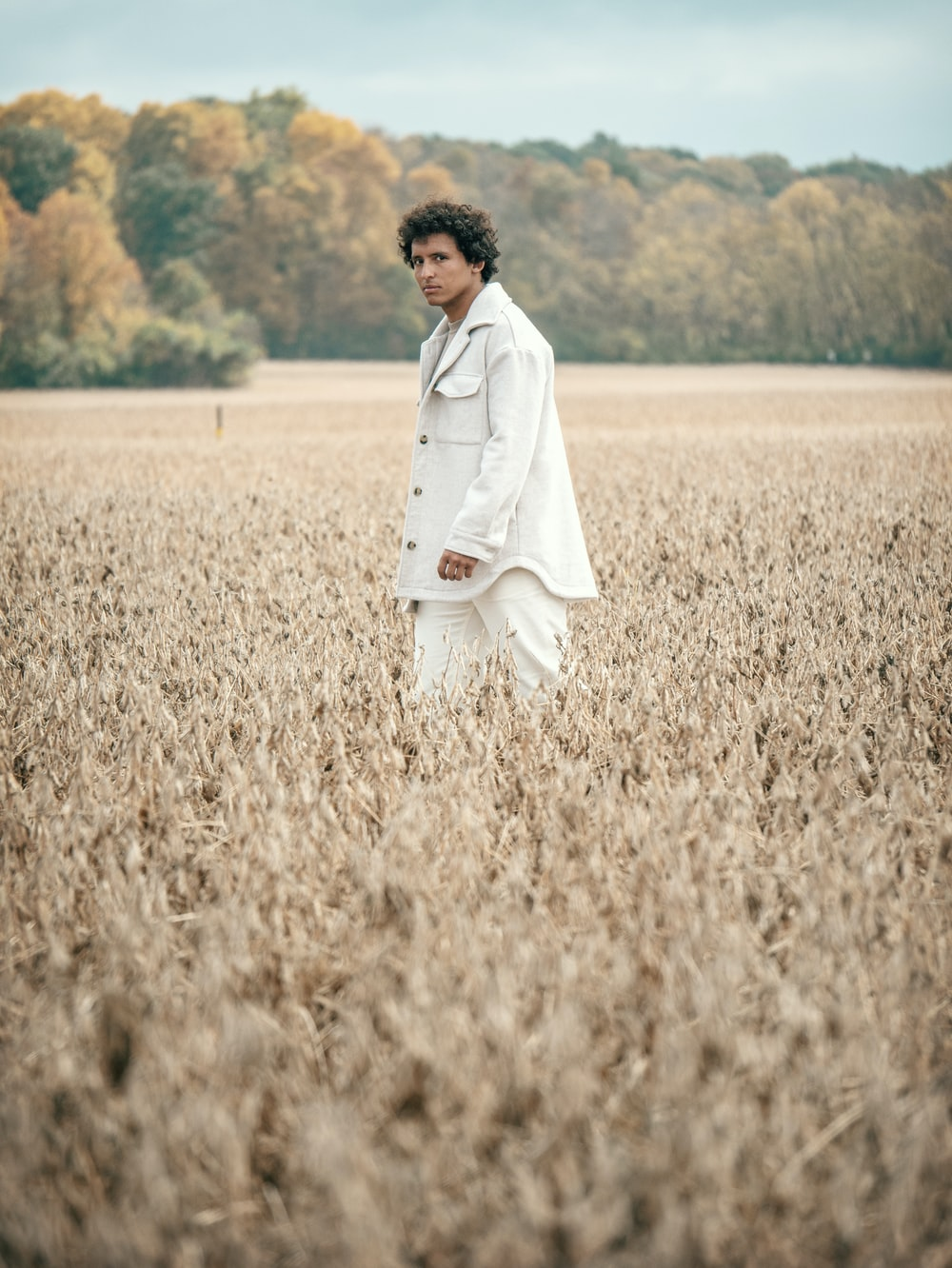 man in white suit walking on brown grass field during daytime
