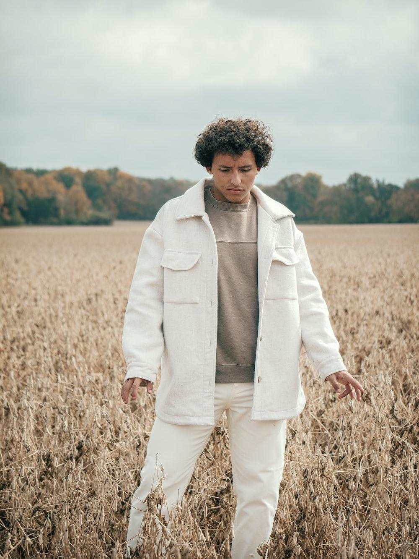 man in white blazer standing on brown grass field during daytime