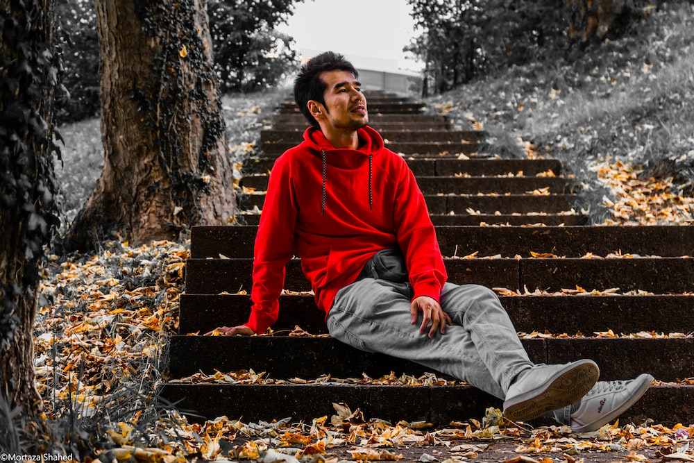 man in red hoodie sitting on brown concrete stairs