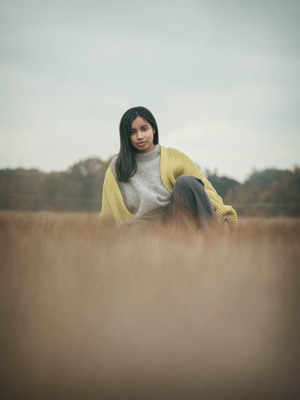woman in yellow hijab standing on green grass field during daytime