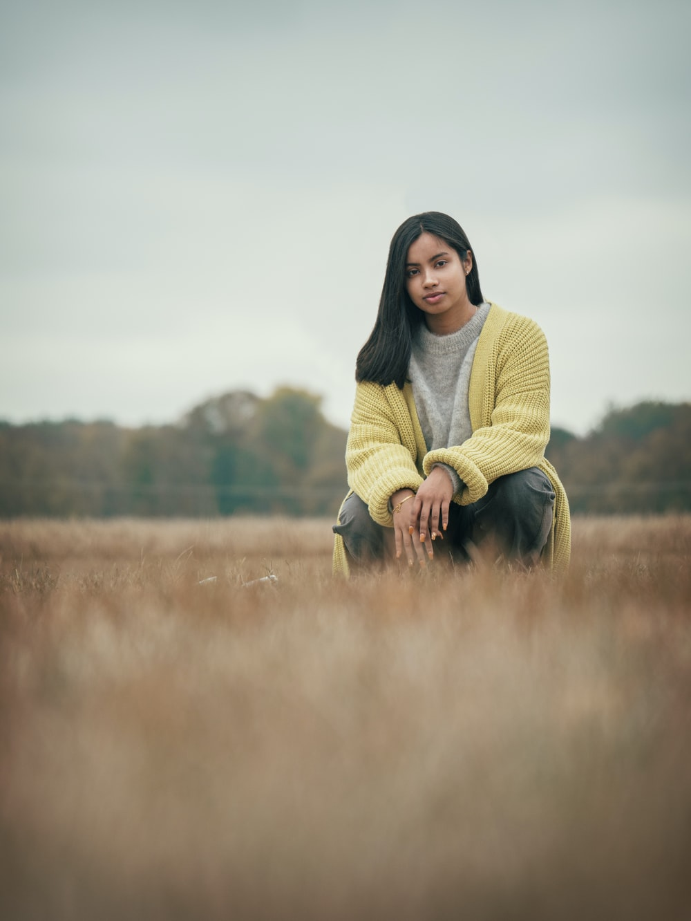 woman in yellow sweater and black pants standing on brown grass field during daytime