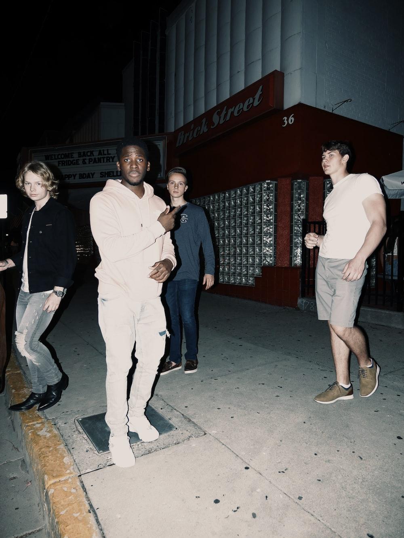 3 men and 2 women standing on gray concrete floor