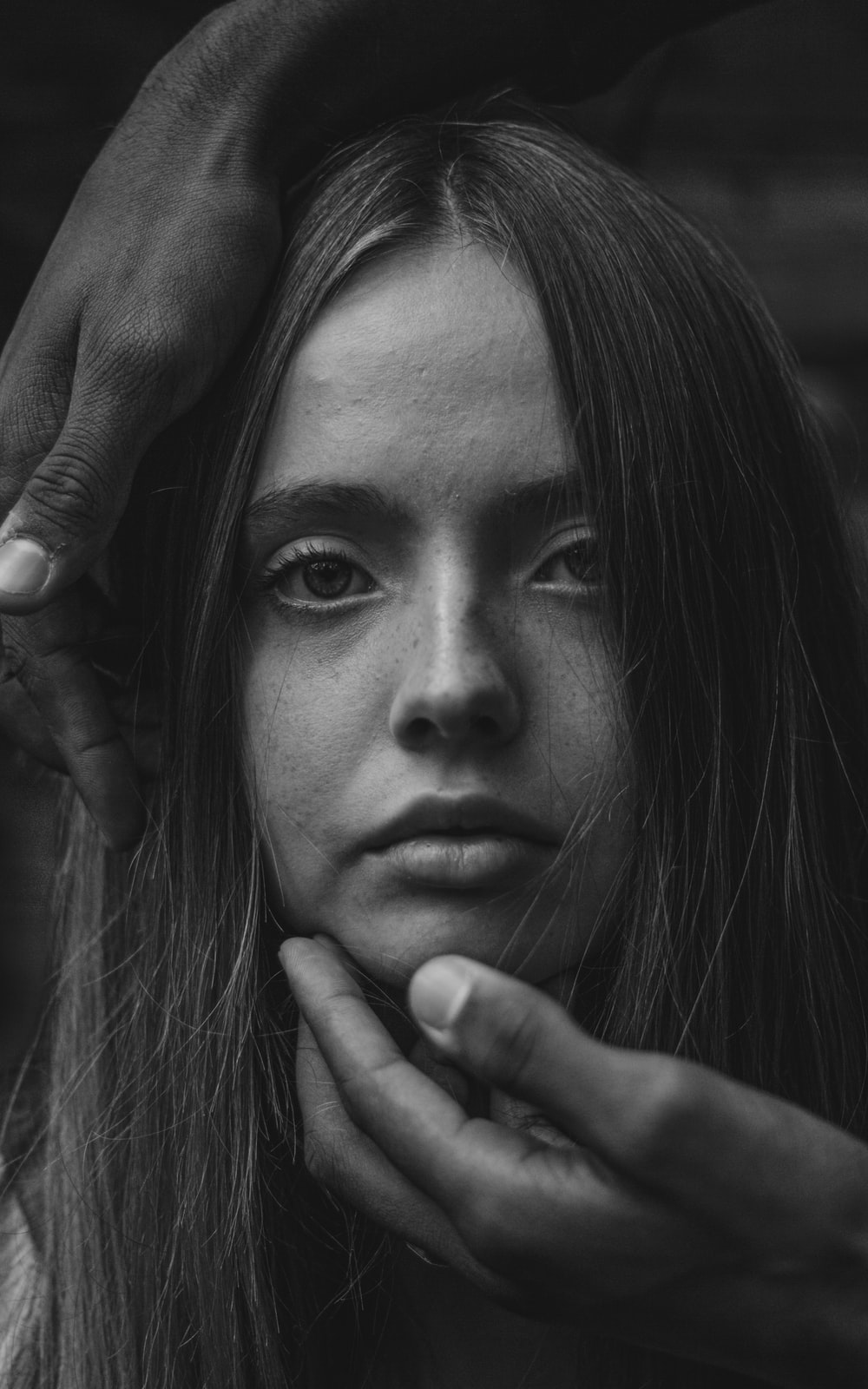 grayscale photo of woman with her hand on her face