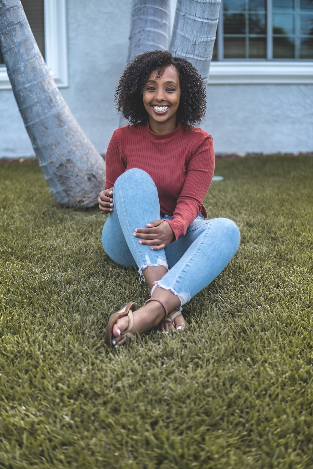 woman in red sweater and blue denim jeans sitting on green grass field during daytime