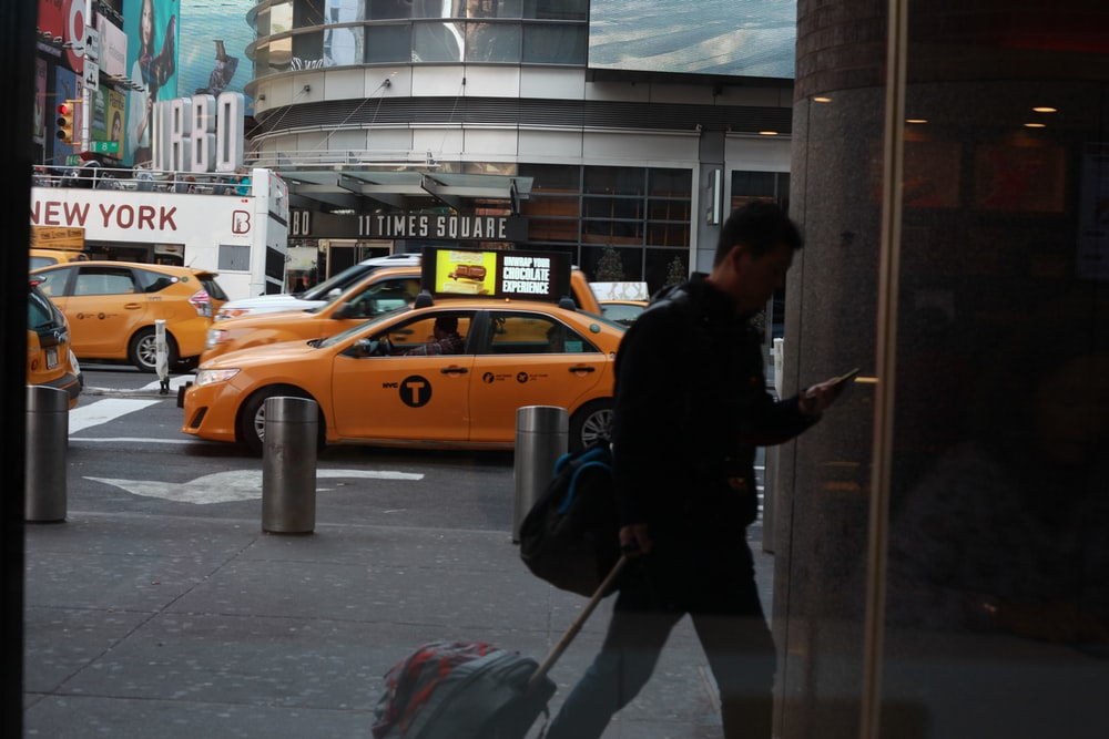 man in black jacket and black pants holding stick near yellow taxi cab
