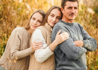 man in gray sweater hugging woman in gray sweater
