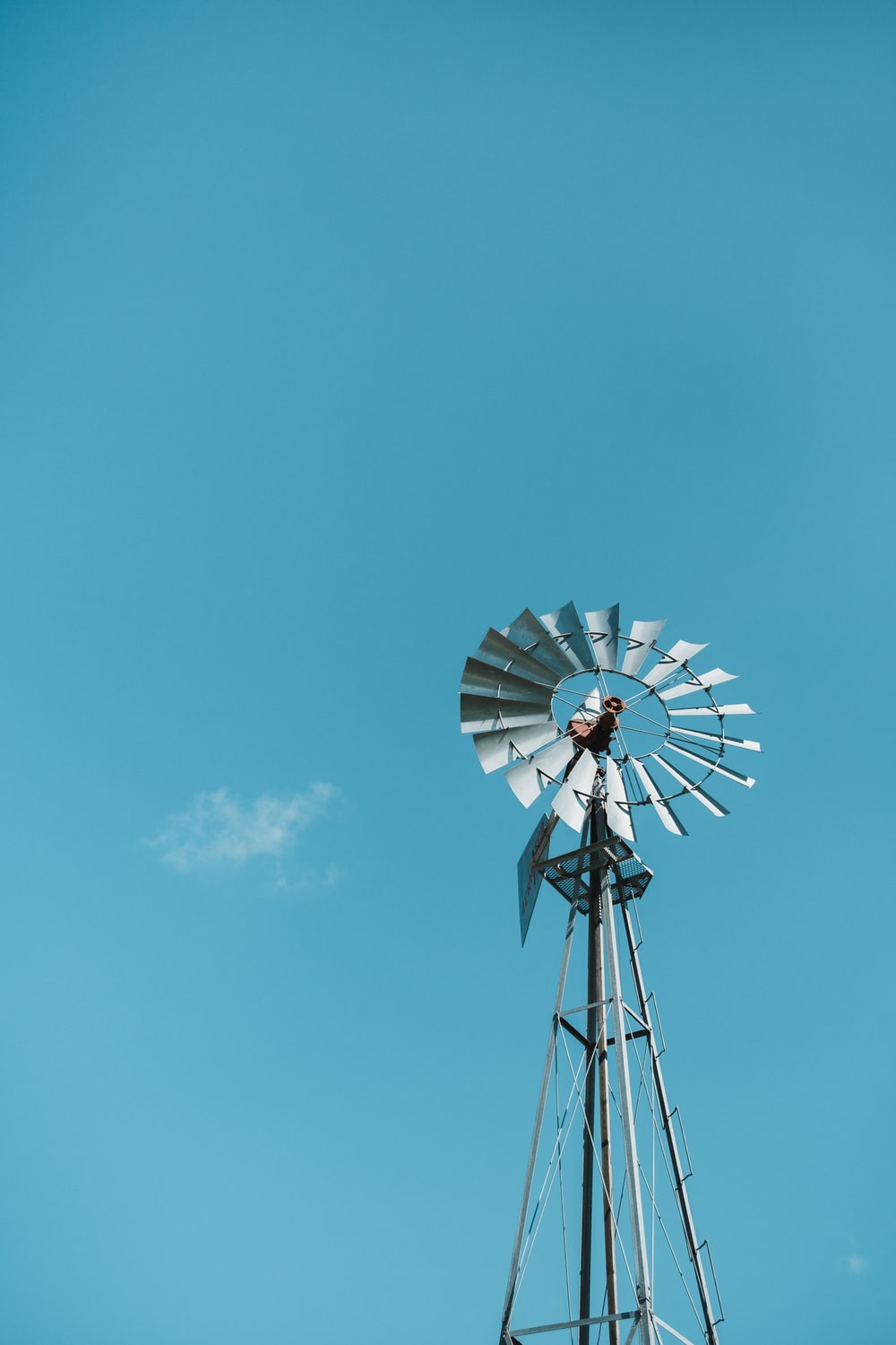 white and black windmill under blue sky during daytime