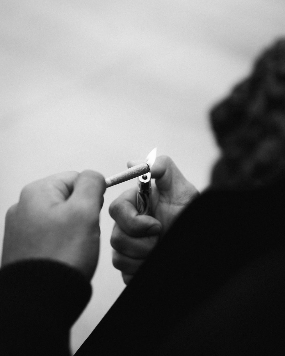 grayscale photo of person smoking cigarette