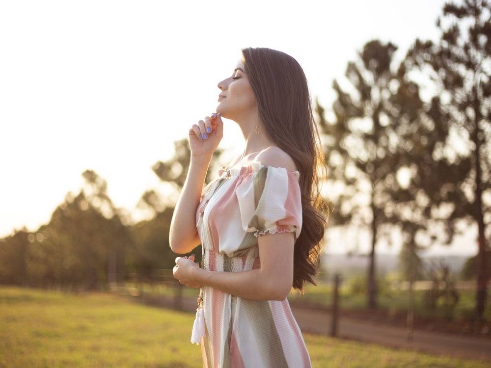 woman in white and pink dress standing on green grass field during daytime