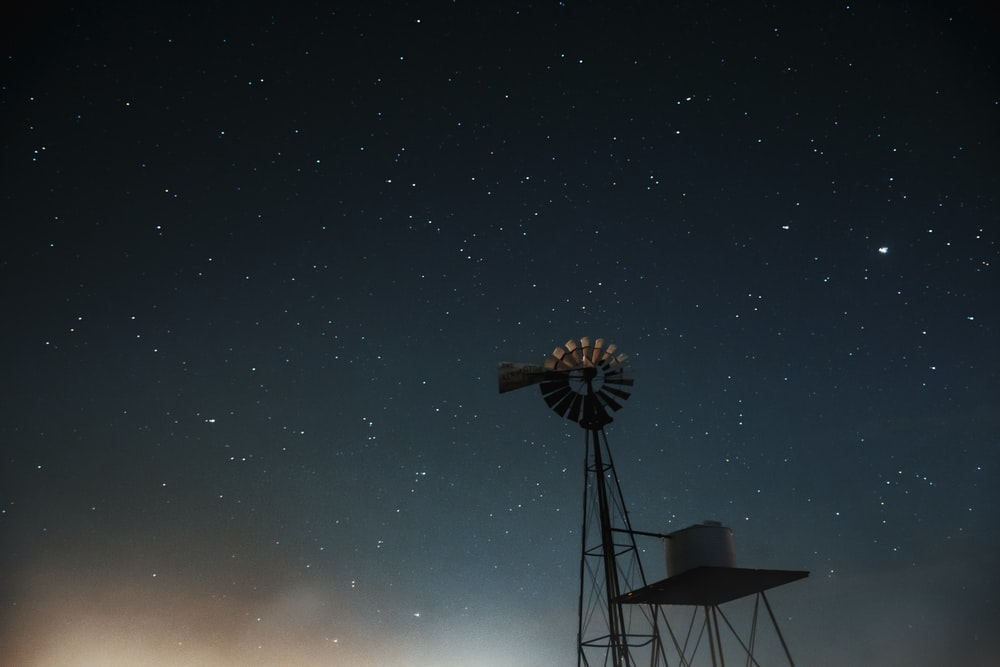 silhouette of windmill under starry night