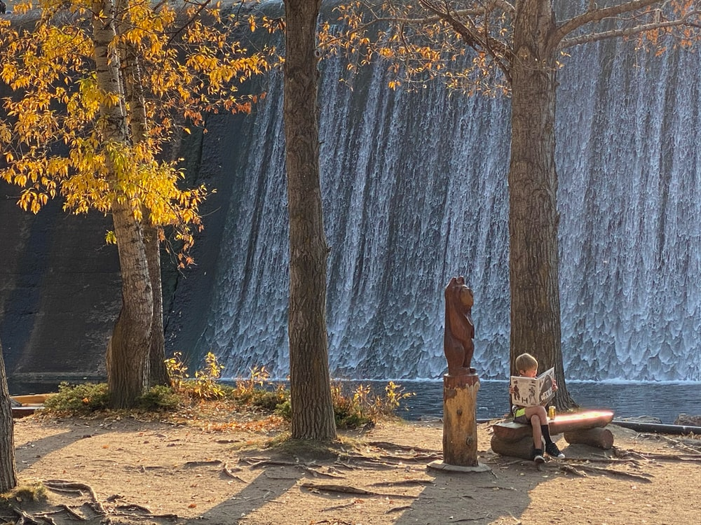 woman in brown dress sitting on bench near body of water during daytime