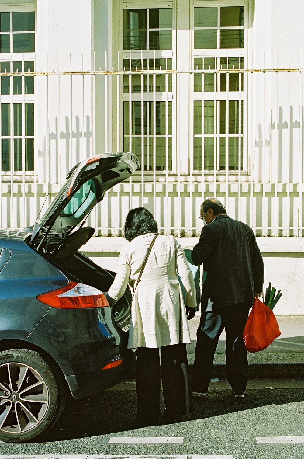 man and woman standing beside black car during daytime