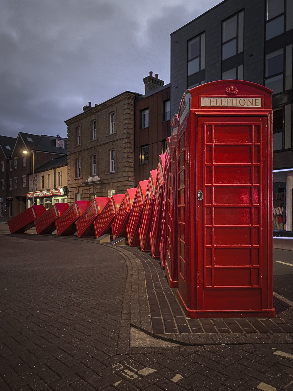 red telephone booth on gray concrete road