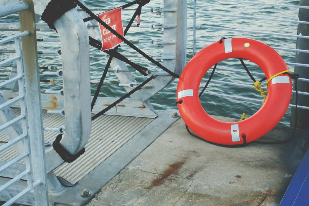 red and white inflatable ring on brown wooden dock