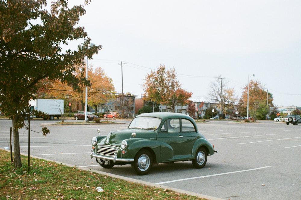 green sedan on gray asphalt road during daytime