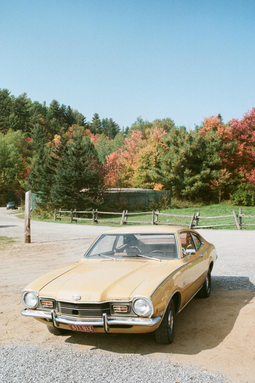 brown and white vintage car parked on gray asphalt road during daytime