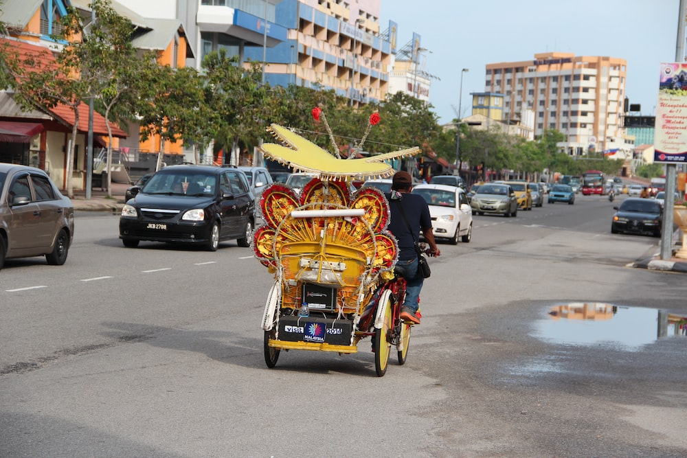 people riding on red and yellow trike on road during daytime