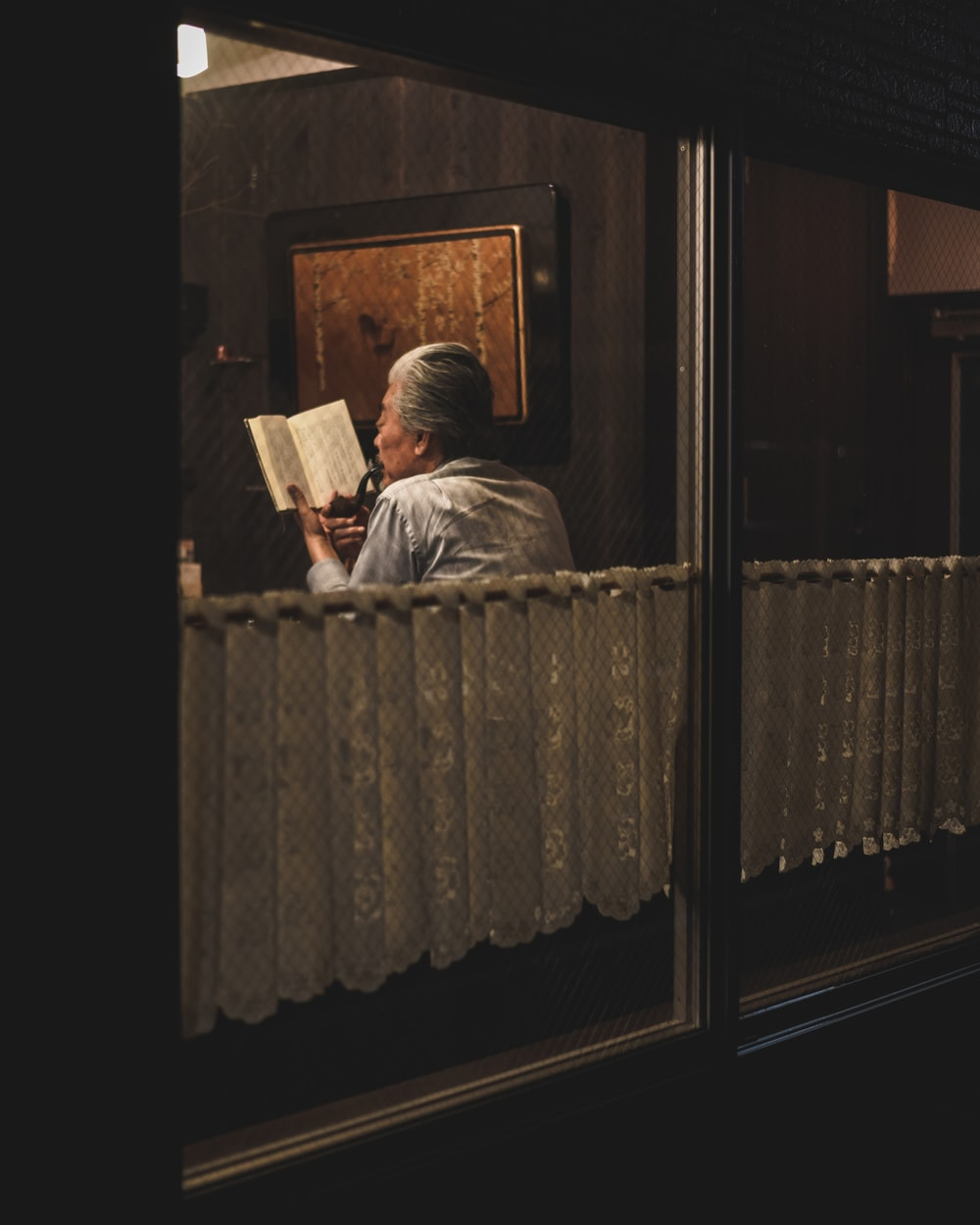 man reading book sitting on chair