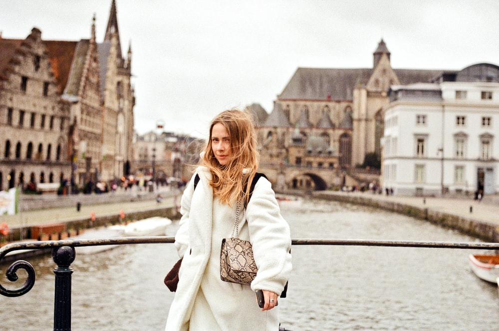 woman in white coat standing near body of water during daytime