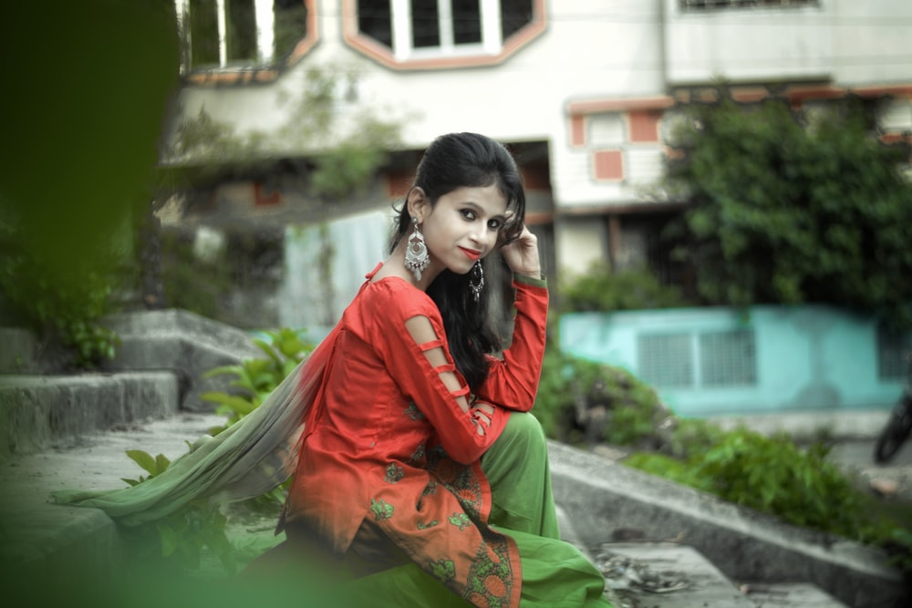 woman in red and green sari sitting on gray concrete bench during daytime