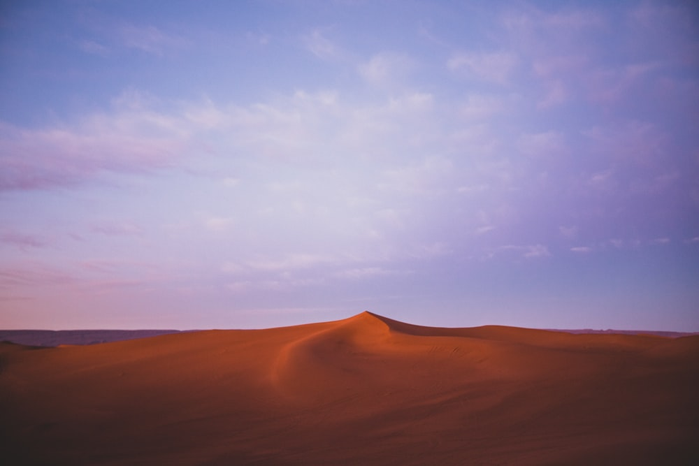 brown sand under white clouds and blue sky during daytime