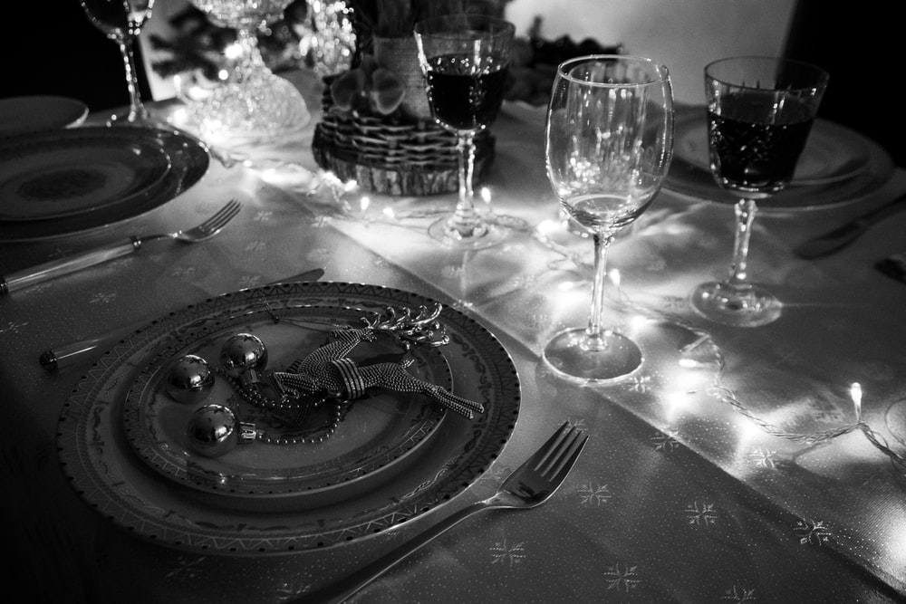grayscale photo of stainless steel fork and bread knife on round plate beside wine glass