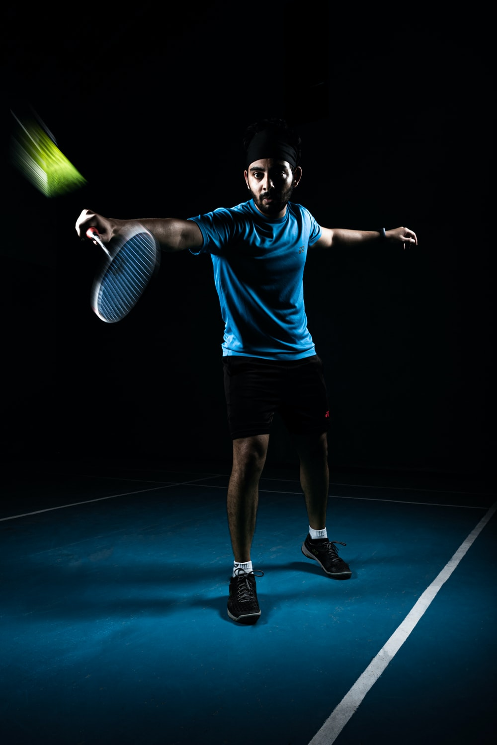 man in blue crew neck t-shirt and black shorts holding green tennis racket