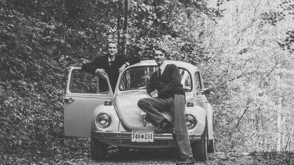 grayscale photo of man in black jacket sitting on car