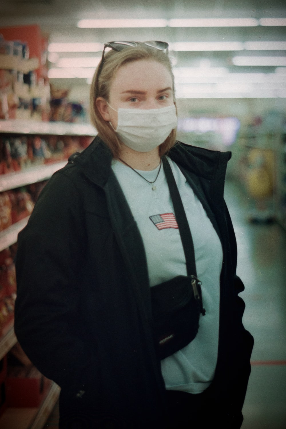 woman in black jacket wearing white face mask